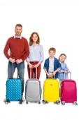 Fotografie Rodinné postavení šťastný zrzka s barevné kufry a usmívá se na kameru izolované na bílém