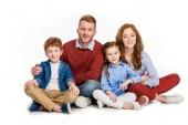 boldog család, két gyerek ül össze, és mosolyogva elszigetelt fehér kamera