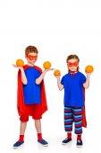 rozkošné malé děti v superhrdina kostýmy drží pomeranče izolované na bílém
