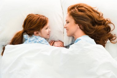 beautiful redhead mother and daughter lying in bed and smiling each other