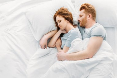 top view of beautiful redhead couple sleeping together in bed