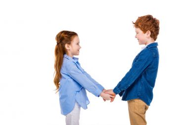 adorable happy children holding hands and smiling each other isolated on white