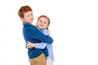adorable redhead children hugging and smiling at camera isolated on white