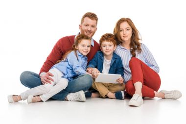 happy redhead family using digital tablet and smiling at camera isolated on white