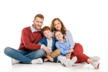 happy redhead family with two kids sitting together and smiling at camera isolated on white