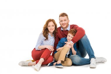 happy parents with cute little son sitting together and smiling at camera isolated on white