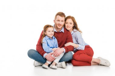 happy parents with cute little daughter sitting together and smiling at camera isolated on white