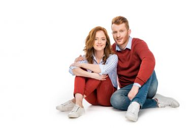 beautiful happy redhead couple sitting together and smiling at camera isolated on white