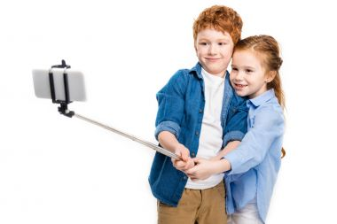 beautiful happy redhead kids taking selfie with smartphone isolated on white
