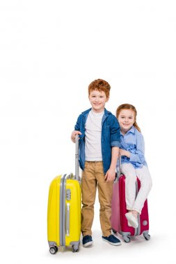 adorable happy redhead children with suitcases smiling at camera isolated on white