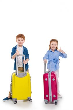 Adorable smiling redhead kids standing with suitcases and showing thumbs up isolated on white stock vector