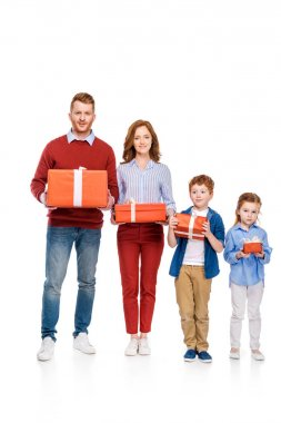happy red haired family holding gifts and smiling at camera isolated on white