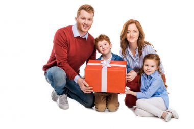 happy redhead family holding big gift box and smiling at camera isolated on white
