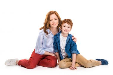 happy redhead mother and son sitting together and smiling at camera isolated on white