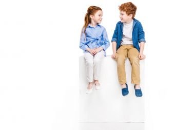 adorable little children sitting on white cube and smiling each other isolated on white