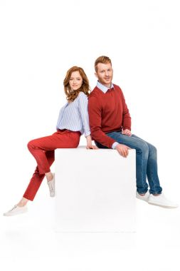 full length view of happy redhead couple sitting on white cube and smiling at camera isolated on white