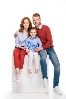 happy redhead family sitting on white cube and smiling at camera isolated on white