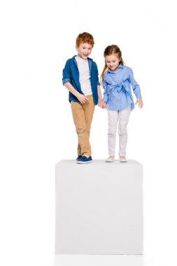 adorable little kids holding hands and standing on white cube isolated on white