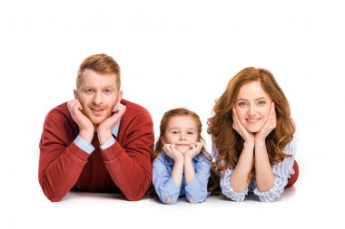 happy redhead family with one child lying together and smiling at camera isolated on white