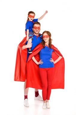 super family with one child in masks and cloaks smiling at camera isolated on white