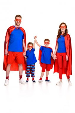 full length view of happy super family in masks and cloaks holding hands and looking at camera isolated on white