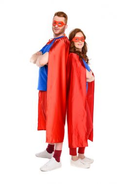full length view of couple of superheroes in costumes standing with crossed arms and looking at camera isolated on white