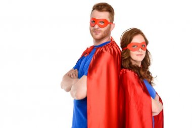 couple of superheroes in costumes standing with crossed arms and looking at camera isolated on white