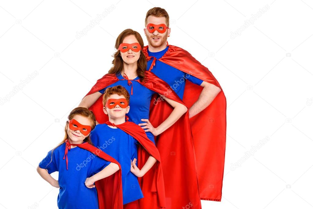 Confident super family in masks and cloaks standing with hands on waist and smiling at camera isolated on white