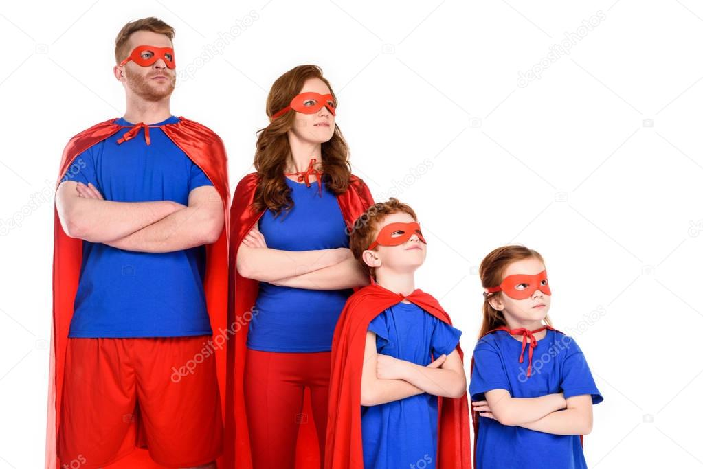 Confident family of superheroes in costumes standing with crossed arms and looking away isolated on white