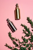 Fotografie top view of metal bottles of perfumes with green branches on pink surface