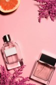 Fotografie top view of bottles of perfumes with pink flowers and orange on pink surface