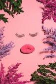 Draufsicht des Gesichts aus Schwamm und falschen Wimpern, umgeben von Blumen auf rosa Oberfläche