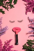 Fotografie top view of face made of sponge with false eyelashes and lipstick surrounded with flowers on pink surface