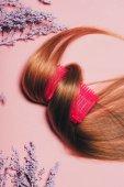 Fotografia vista superiore dei capelli rotolato bigodino con i fiori sulla superficie rosa