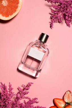 top view of bottle of perfume with pink flowers, orange and strawberry on pink surface