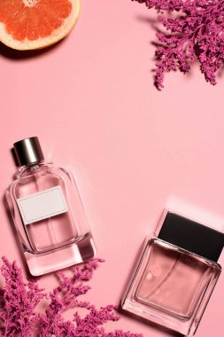 top view of bottles of perfumes with pink flowers and orange on pink surface