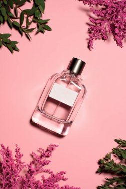 top view of bottle of perfume with flowers and leaves on pink surface