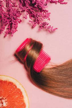 top view of hair rolled over curler with flowers and orange on pink surface