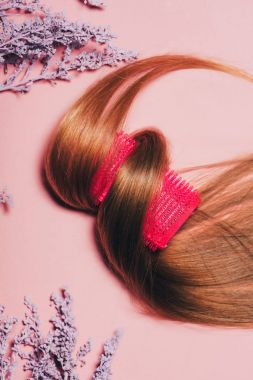top view of hair rolled over curler with flowers on pink surface