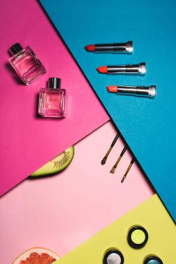 top view of various makeup supplies with fruits on colorful surfaces
