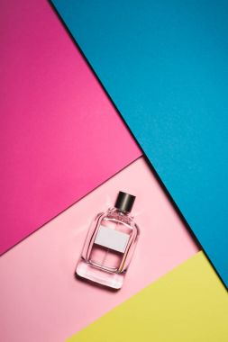 top view of glass bottle of perfume on colorful surface