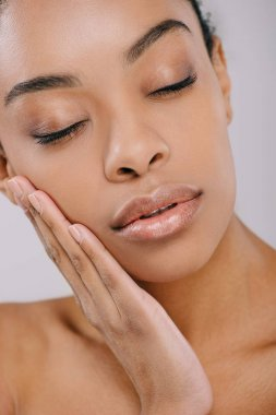 sensual african american woman with perfect skin touching her face isolated on grey