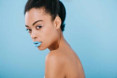 seductive young woman with creative makeup and blue lips looking at camera isolated on blue