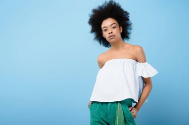 beautiful african american woman in fashionable off-the-shoulder top isolated on blue