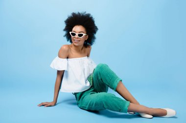 young african american woman in stylish clothes and sunglasses sitting on floor on blue