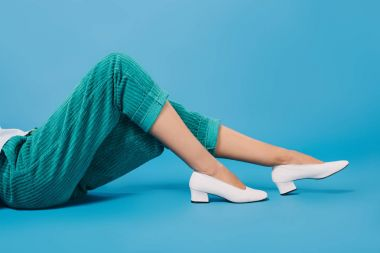 cropped shot of woman in stylish pants and shoes lying on floor on blue