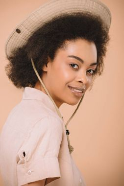 close-up portrait of happy african american woman in safari hat isolated on beige