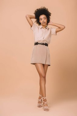 young african american woman in stylish clothes on beige