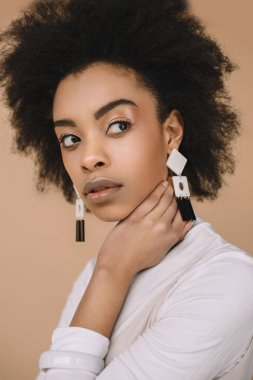 close-up portrait of attractive young woman in stylish clothes with earrings isolated on beige