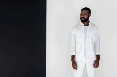 handsome african american man in white stylish clothes looking away